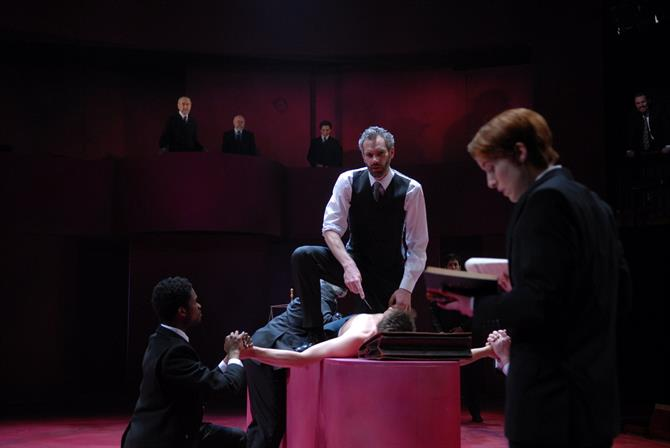 Shylock stands over Antonio with a knife as Portia explains how the bond will be forfeit.