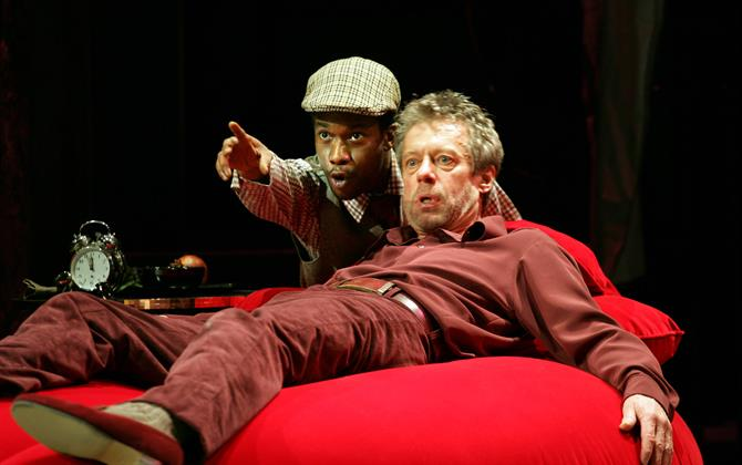 A man points at something over the shoulder of a man reclining on a red beanbag.
