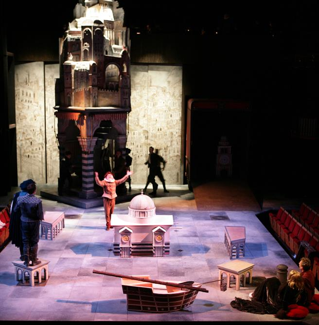 Actors performing on a stage littered with miniature sets.