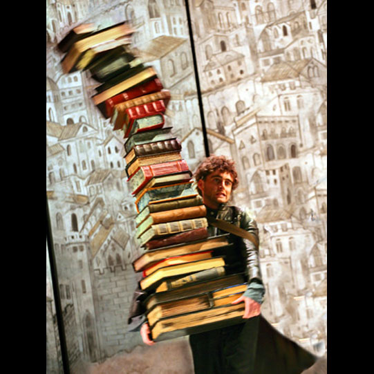 Jack Laskey as Biondello, wearing a long leather coat and carrying a stack of old books taller than himself