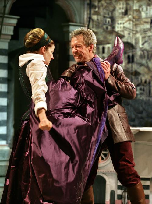 A woman in a purple dress and boots aims a kick at a man's head.