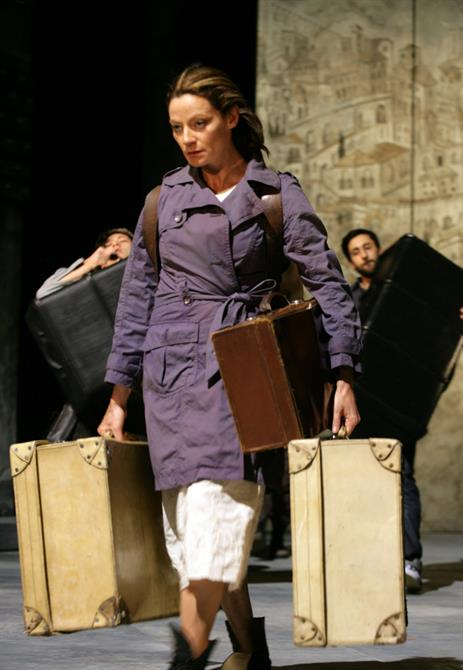 A woman carrying three large suitcases.