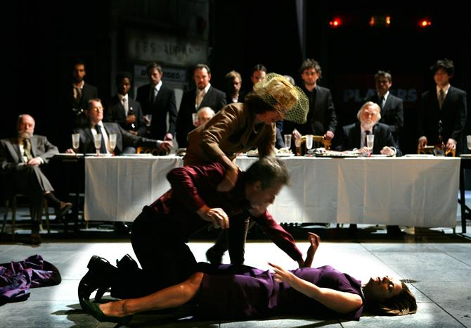 A group of men in suits look at a woman passed out on the floor.