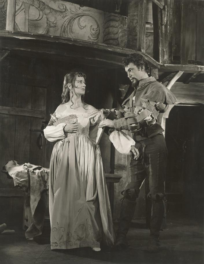 Petruchio, dressed in traditional Renaissance clothes, takes a long dress off Katharine, who looks at him disappointedly