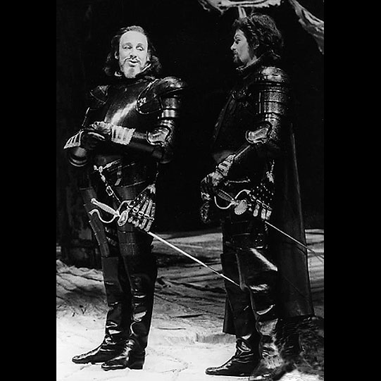 Two men in dark armour with swords at their sides.