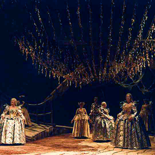 Women in dresses with large bustles under a chandelier.