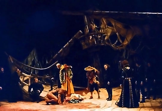 The cast in production on stage in the wreckage of a wooden vessel.