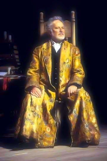 A grey-haired man sits on a wooden chair in a golden robe.