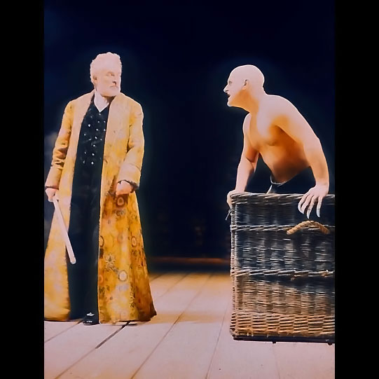 A man in a long yellow cloak looks at a shirtless bald man who leans out of a wicker casket.