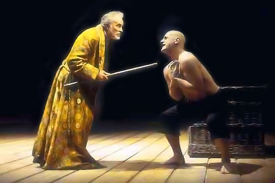 A man in a gold cloak points a staff at a pleading shirtless bald man.
