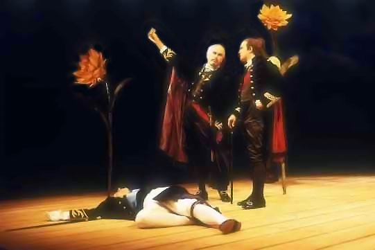 Two men stand over a man lying on the floor.