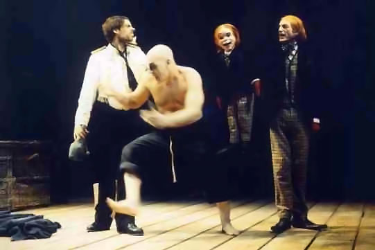 A bald man dances excitedly in front of two other men, one of whom holds a puppet.