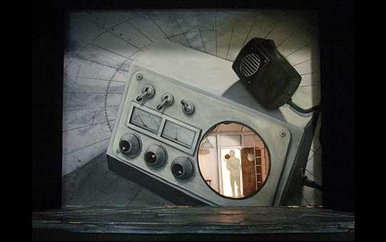 A model of a set with a large painted radio at the back with a person visible through the transparent speaker.