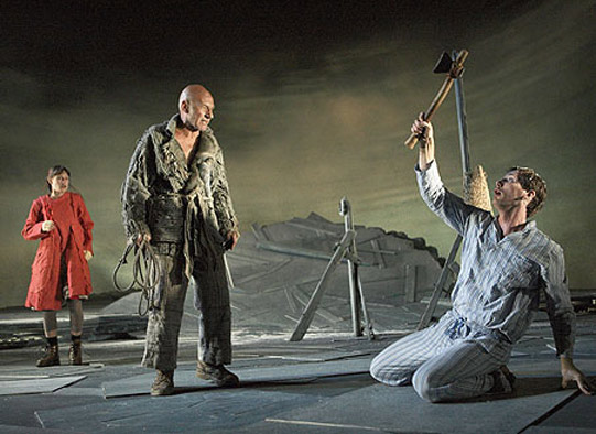 A man and woman look at a man in pyjamas who holds an axe above his head.