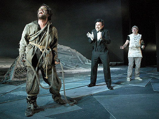 A screaming man in rags is watched by two others.