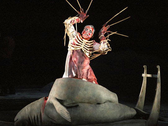 A blood-covered person emerges from the corpse of a seal wearing a bony ribcage and with long skeletal claws raised above their head.
