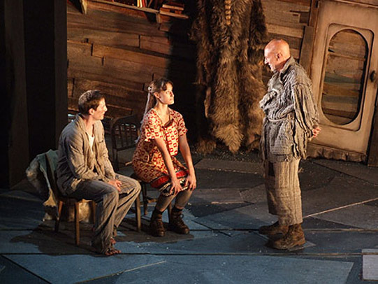 A young man and woman sit on chairs, being spoken to by an older man in rags.