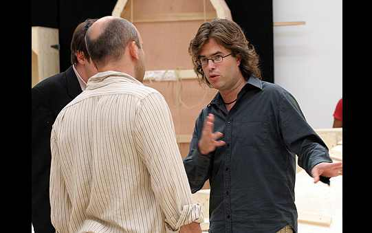 A man gives direction to two of the actors.