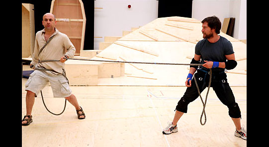 Two men holding a rope in rehearsal.