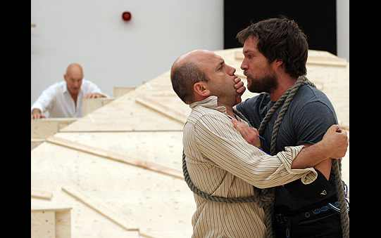 A man holds a hand over another man's mouth in rehearsal.