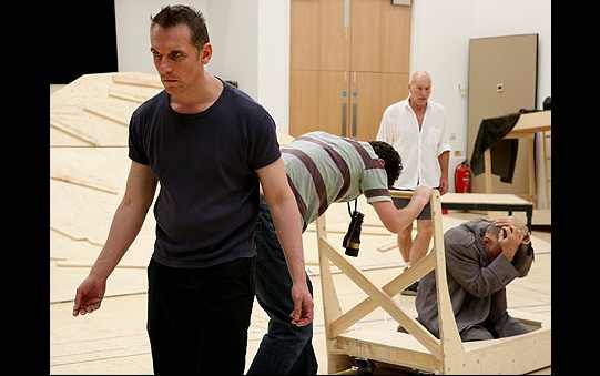The cast in rehearsal, working with wooden props.