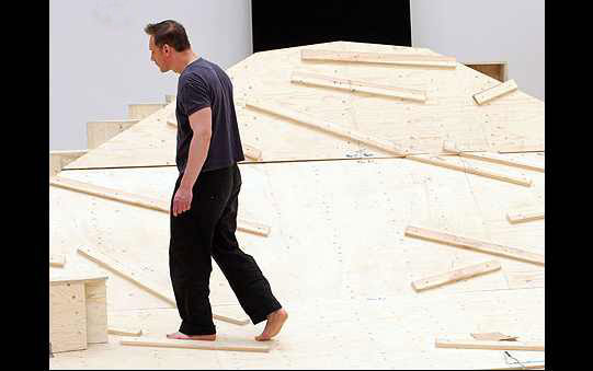 A man walks on the wooden set during rehearsals.