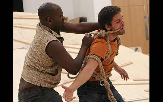 A man restrains another man with a long rope.