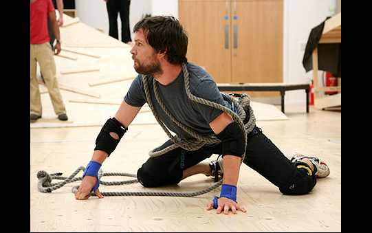 A man crouches on the floor with rope wrapped around him.