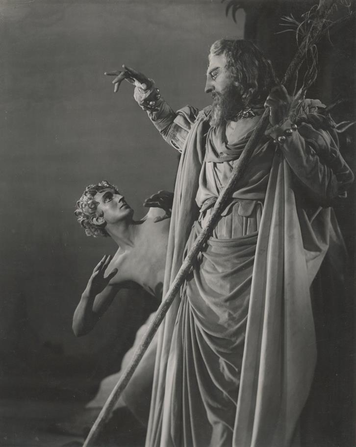 Prospero, who wears robes and carries a long staff, towers over Ariel.