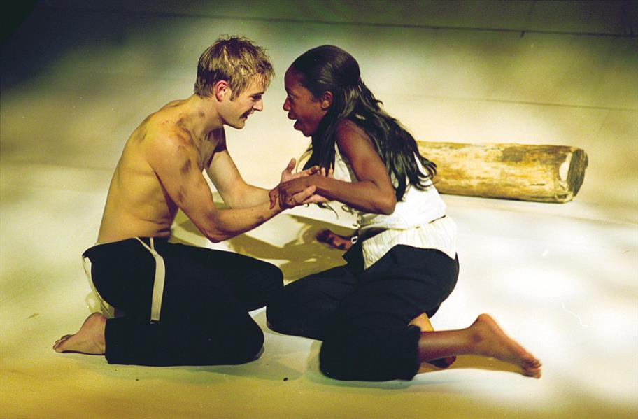 Ferdinand and Miranda kneel on the floor, facing each other and holding hands