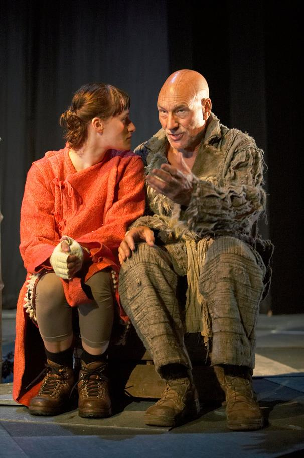 A ragged Prospero sits next to Miranda, who looks at him intently.