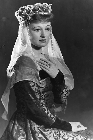 Anna Konstam in an ornate gown with a crown and large ring