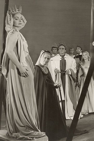 A woman in a long white robe and spiky crown stands on a plinth, watched by other men and women