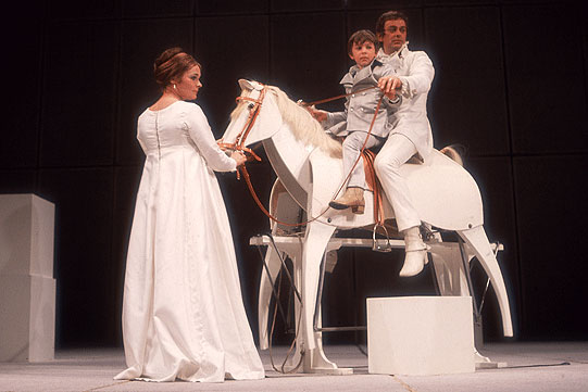 A man and young boy sit on a large wooden horse, as a woman holds the bridle. All are dressed in white.
