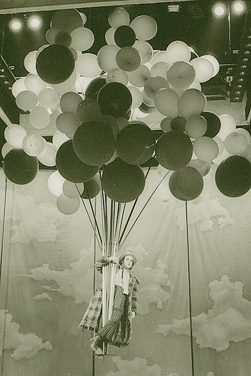 A man is carried aloft by a large cloud of coloured balloons