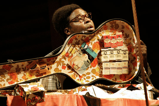 A man holds open a guitar case to show a colourful interior covered with cigarette boxes and a lewd postcard