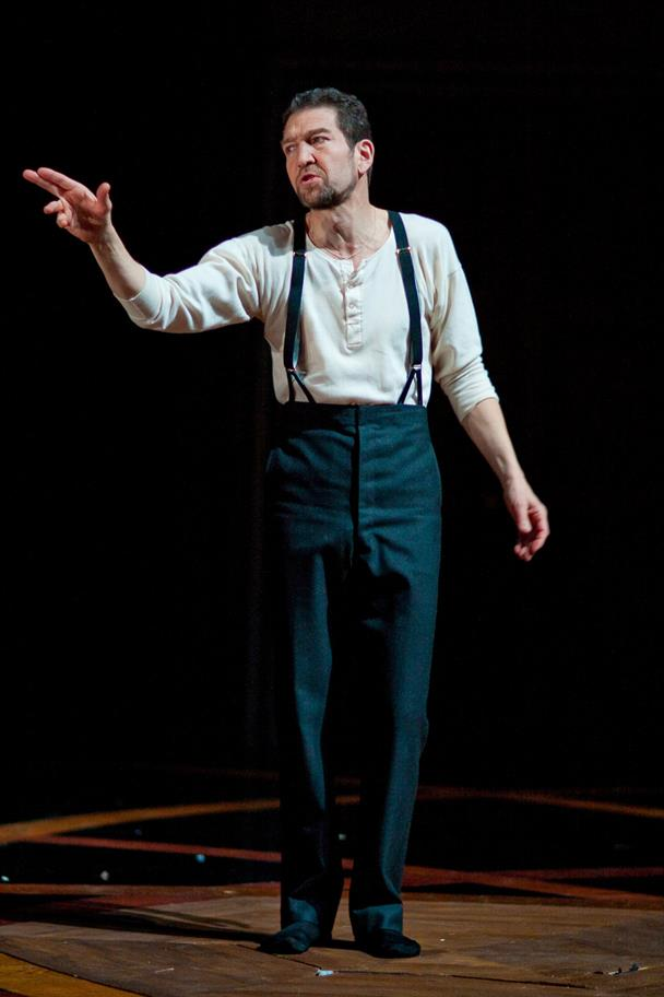 Greg Hicks stands in black trousers and a white shirt with black suspenders