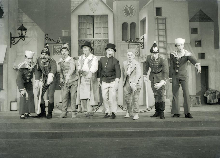 The cast of The Comedy of Errors stand in a row, left foot forward, singing as a group