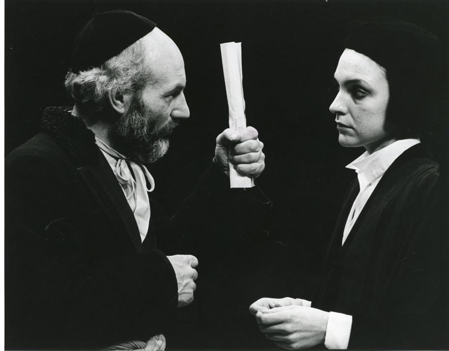 A man in a skullcap brandishes a scroll at a woman in dark clothes