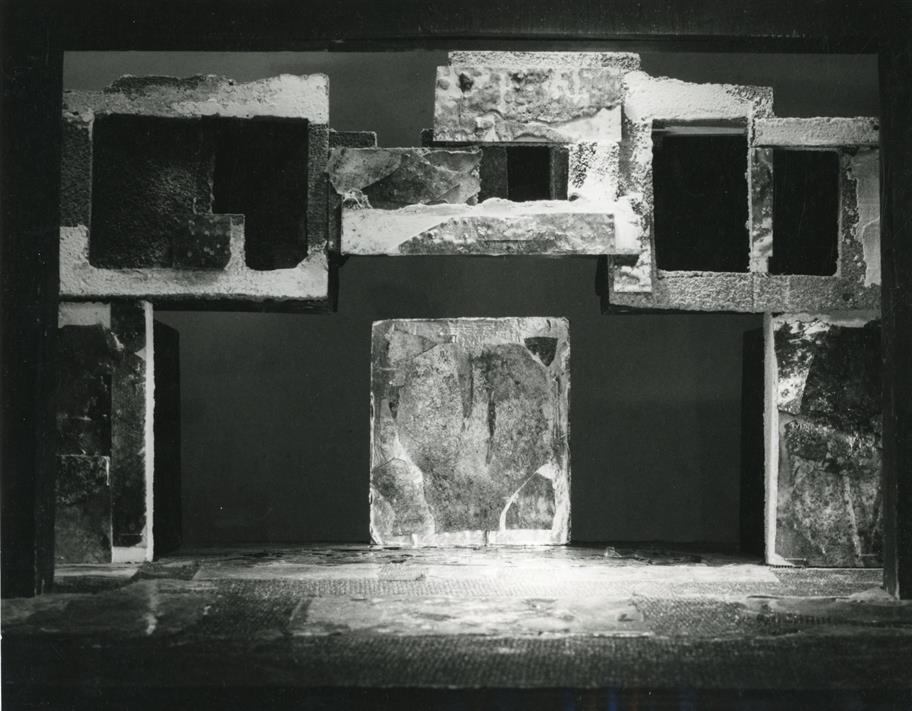 A theatrical set featuring square concrete hollow blocks arranged asymmetrically and a central door at the back