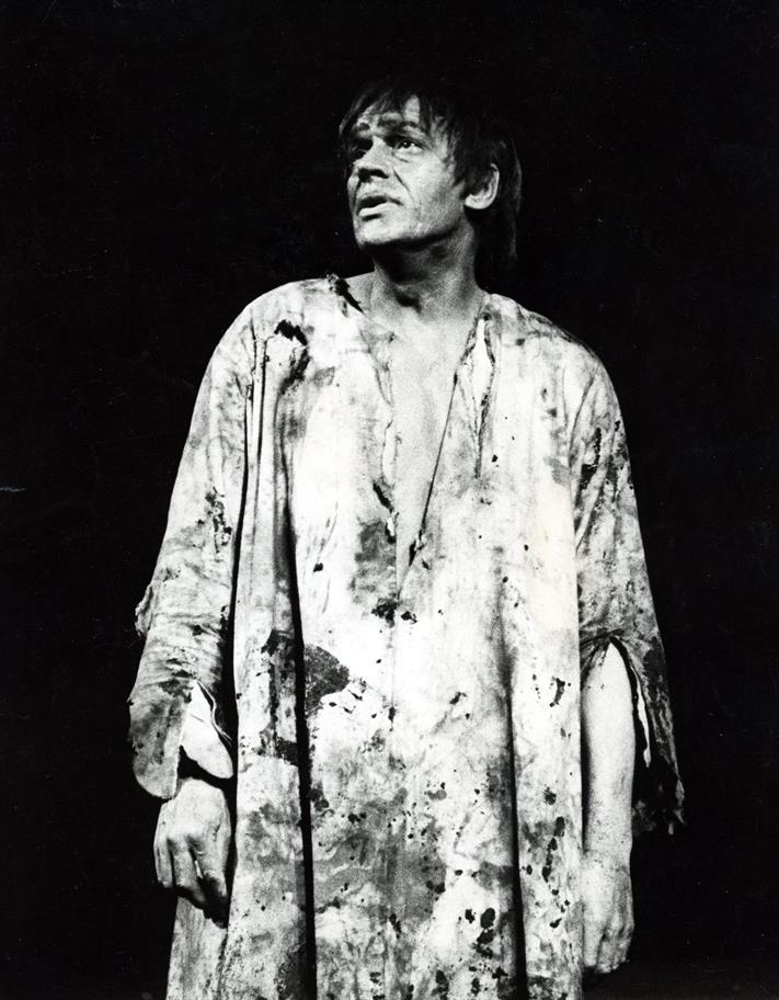 A man in ragged dirty long robe stands disconsolately
