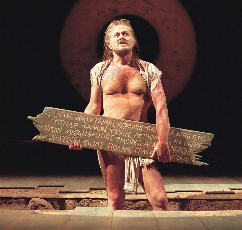 Michael Pennington standing centre-stage dressed in rags and holding a wooden sign with Greek script on