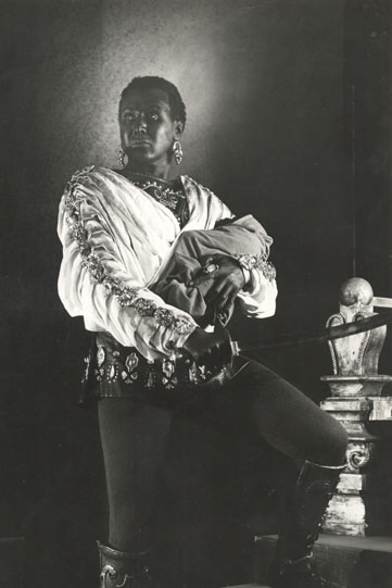 Production image of Anthony Quayle as Aaron, in a doublet and with a sword.
