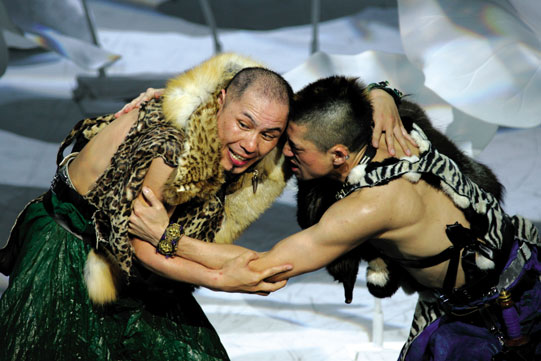 Production image of actors wrestling in a Japanese production of the play.