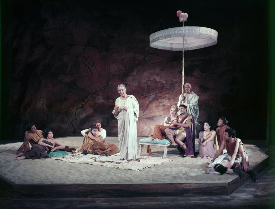 A man in toga stands speaking or singing to a several couples sitting on a sandy surface, one couple sitting on a recliner with parasol