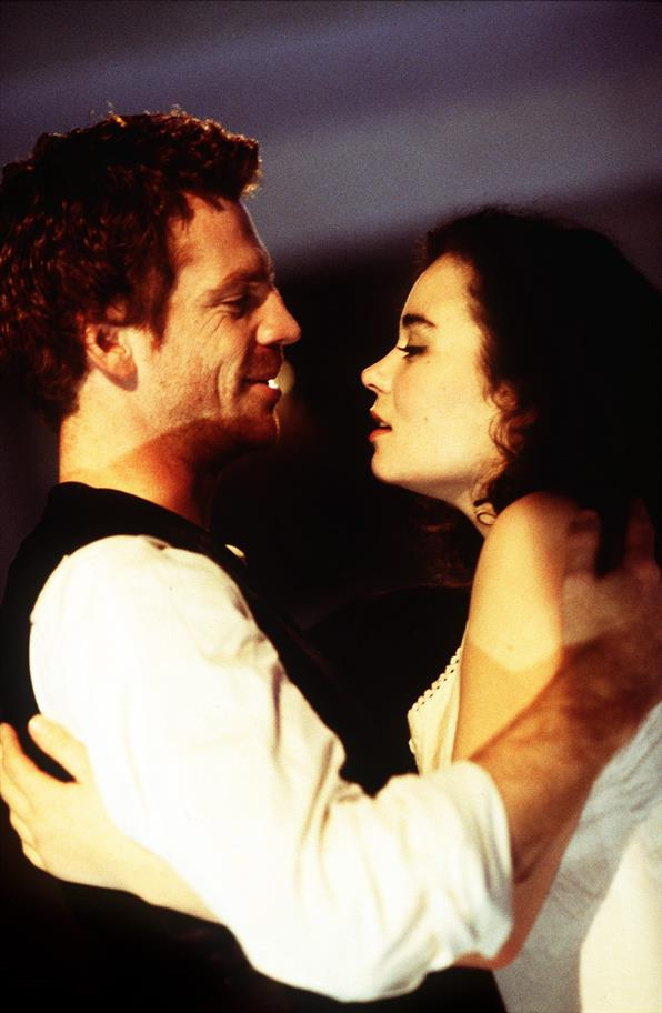 A man in a white shirt and black vest holds a young woman in a white slip, smiling