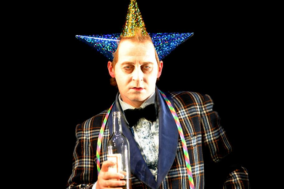 A man with a pale powdered face wearing three party hats and holding a glass bottle