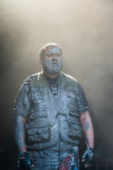 A man covered in grey paint on a smoky stage