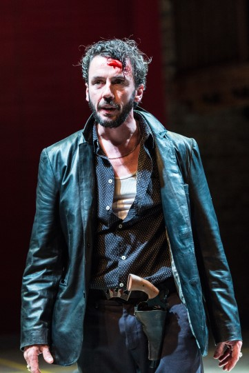 A man with blood on his head and a gun in a holster under his leather jacket