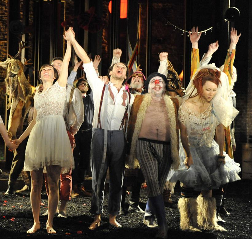 The cast of As You Like It, wearing festive clothing and throwing their arms up in the air